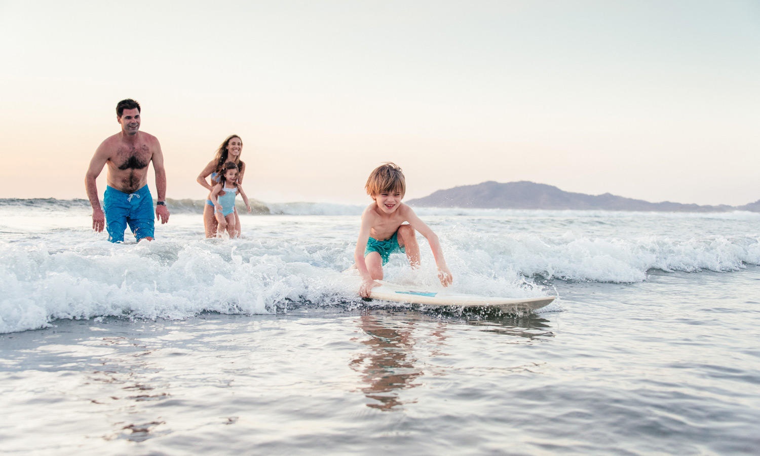 Young boy learning to surf as his family watches in Tamarindo, Costa Rica. Photographed by brand photographer Kristen M. Brown, Samba to the Sea.