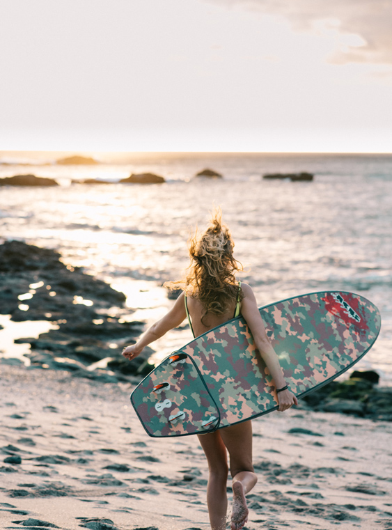 Female surfing running on the beach with her surfboard in Tamarindo, Costa Rica. Photographed by brand photographer Kristen M. Brown, Samba to the Sea.