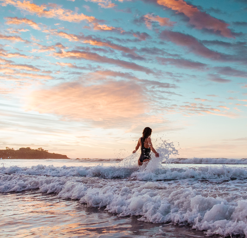 Woman walking into the ocean in Tamarindo, Costa Rica. Photographed by brand photographer Kristen M. Brown, Samba to the Sea.